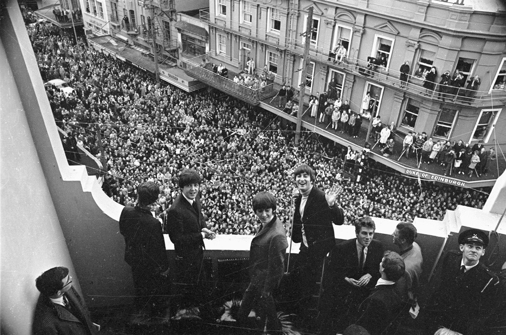The Beatles smile at the camera on the Town Hall balcony, while a crowd watches on from the street.